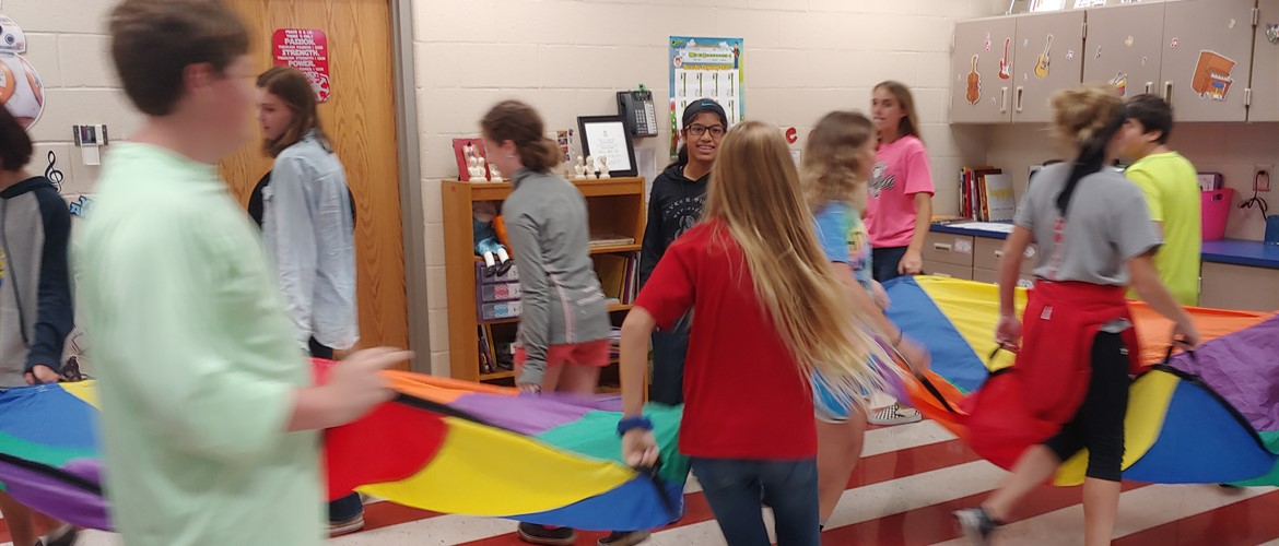 Students dancing to flow of music with a parachute.