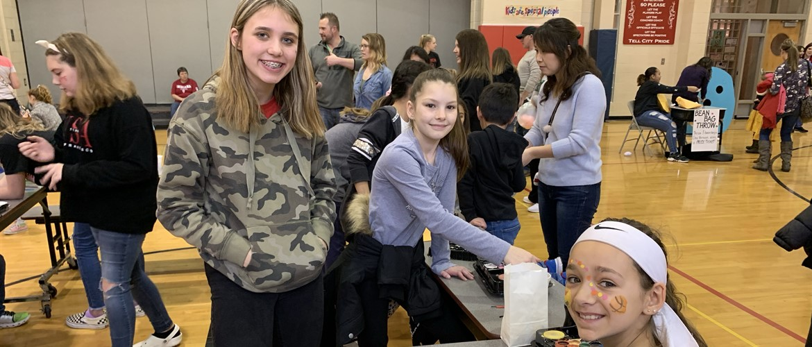 Students pose during a break in face painting at the Winter Carnival.