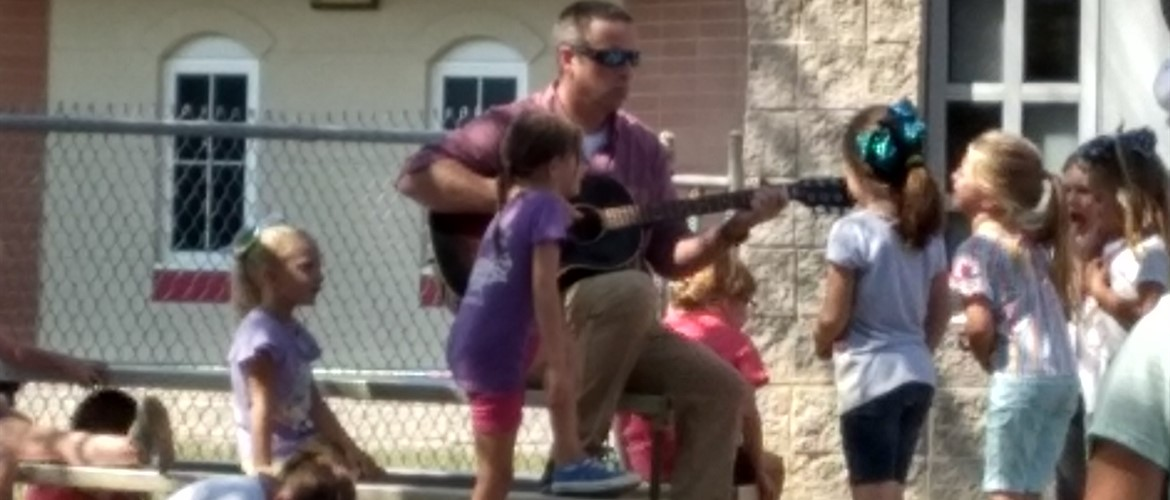 Mr. Mike playing guitar for students.