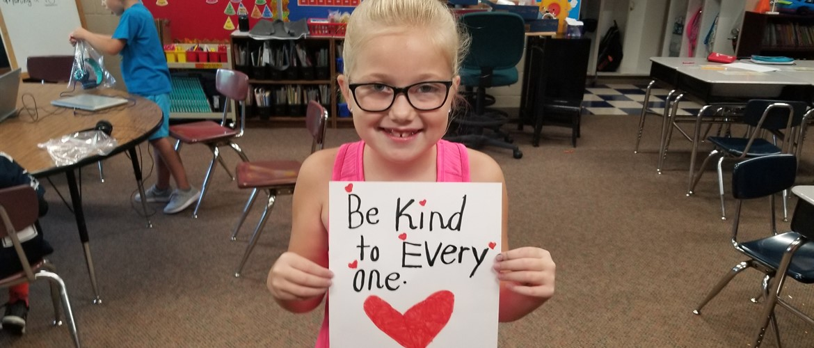 Student with a Be Kind to Everyone poster.