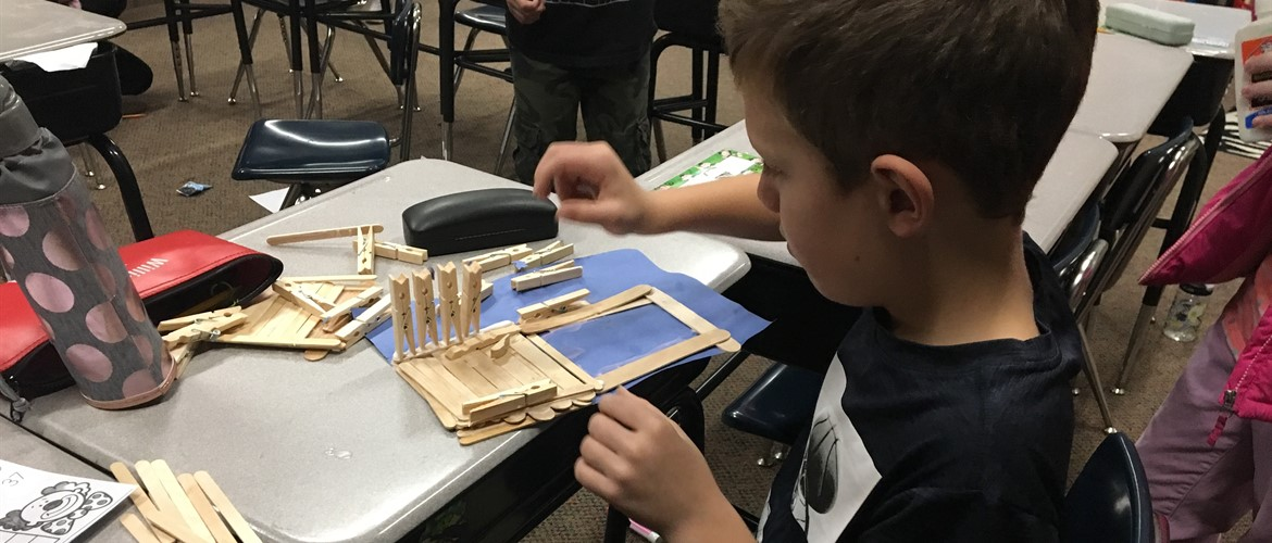 Student making project out of clothespins, popsicle sticks, and glue.