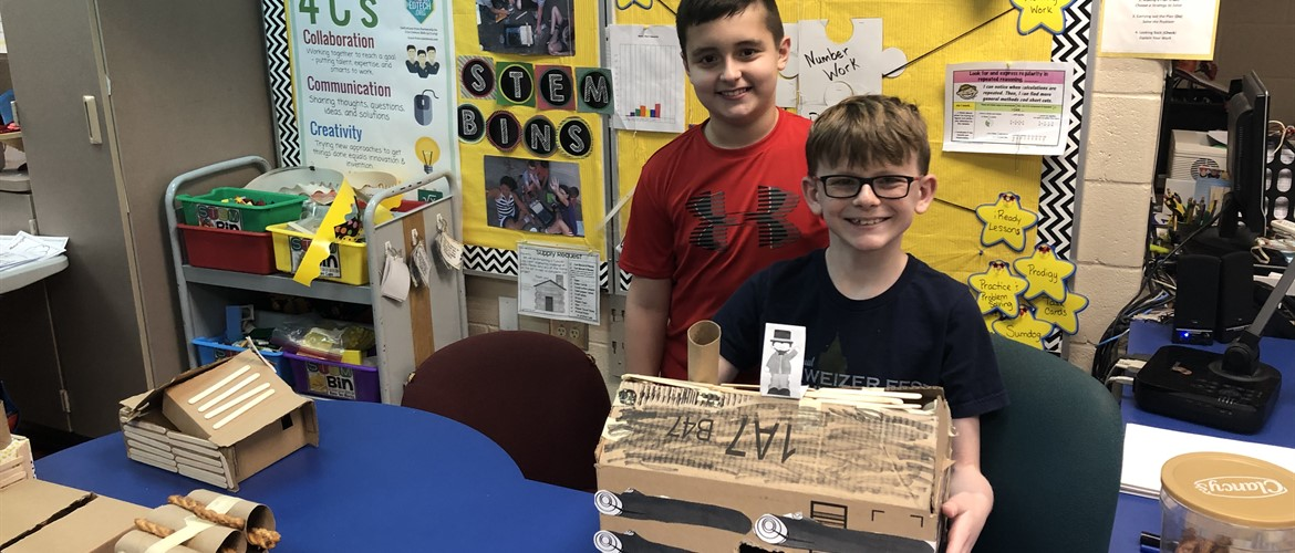 Students pose with their log cabin made of cardboard.