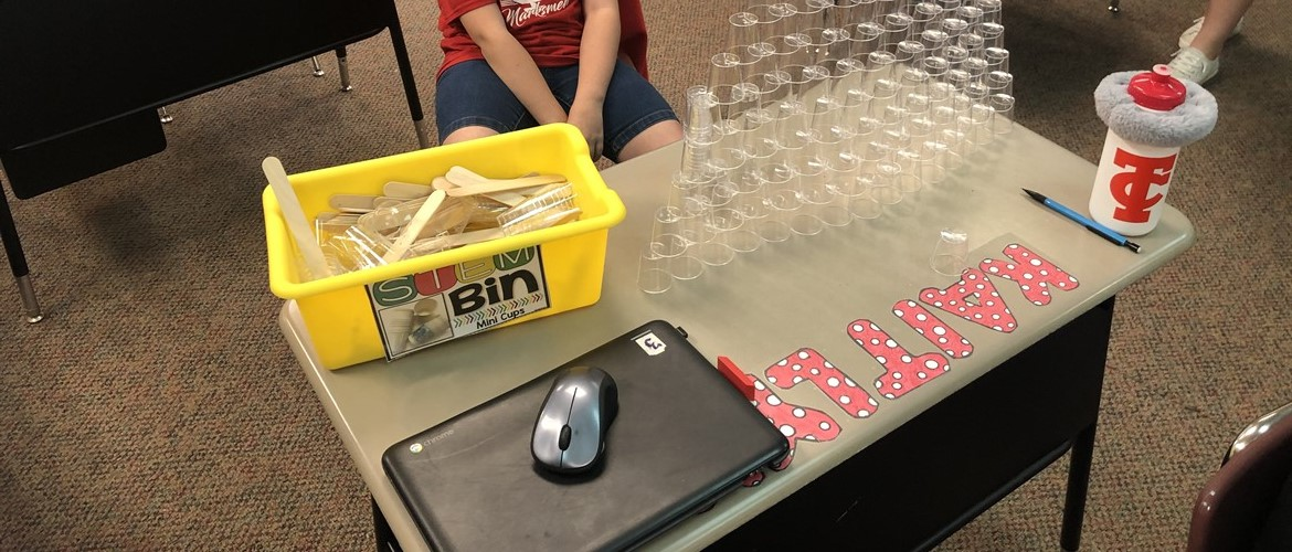 Student using cups from a STEM bin to stack them.