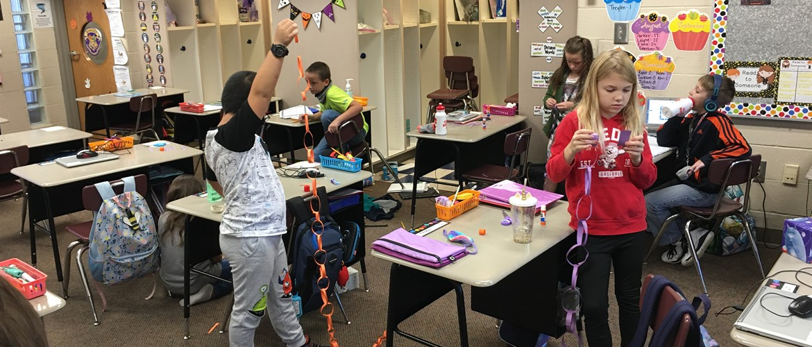 Students make a paper chain.