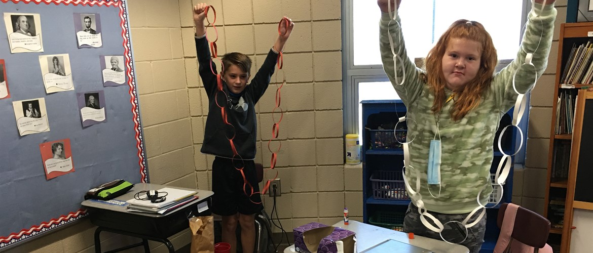 Students show their paper chain.