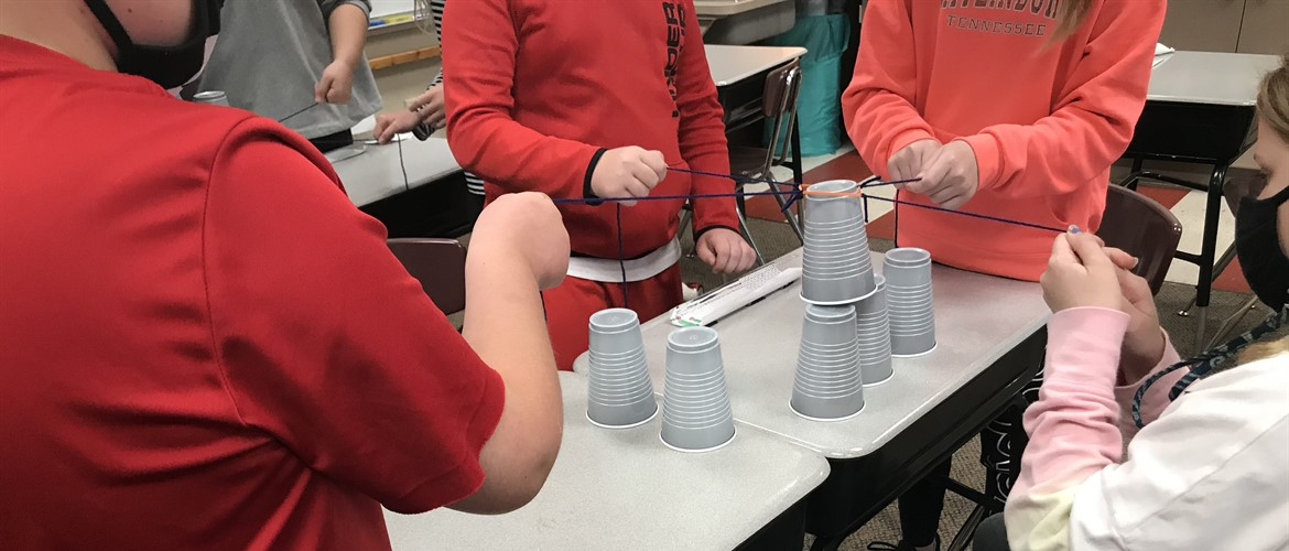 Students try to stack cups with 4 team members and a rubber band.