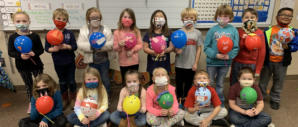 Students with miniature floats made out of balloons.