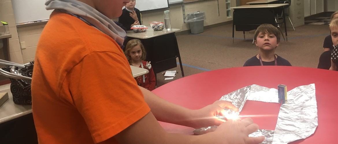 Student creating light from aluminum foil and battery.