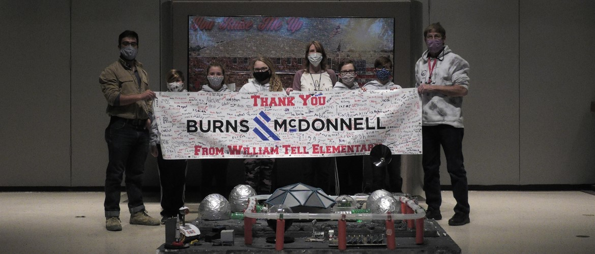 Students on the Future City team pose with a banner thanking Burns-McDonnell.