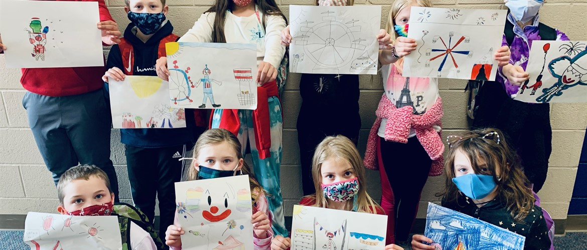 Students displaying artwork.