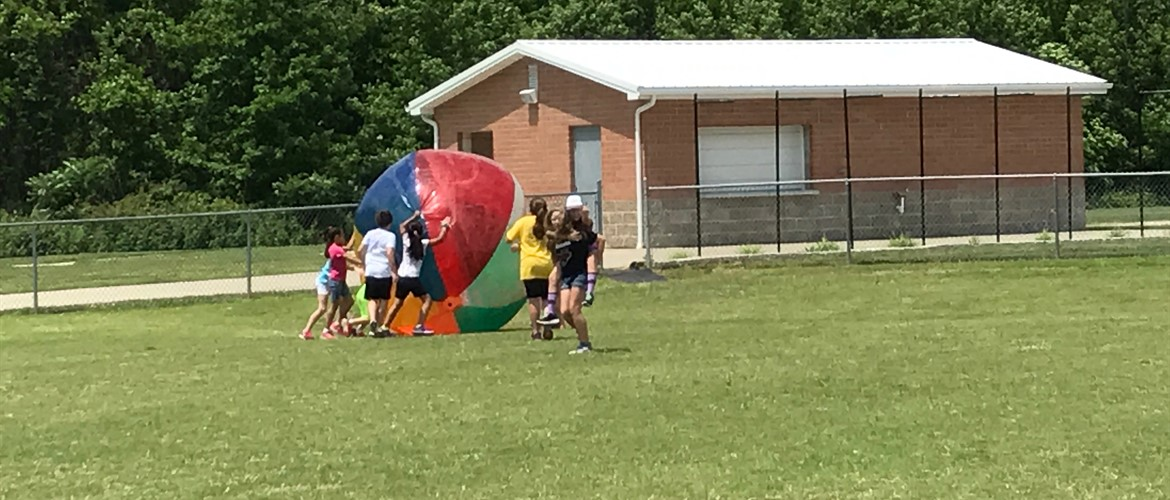 Students roll a gigantic beach ball around on the last day of school.