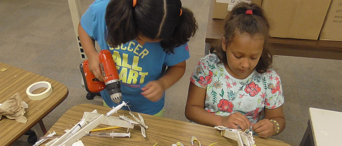 Autumn and Hannah construct a hydraulic robot arm for WTE STEM Camp.