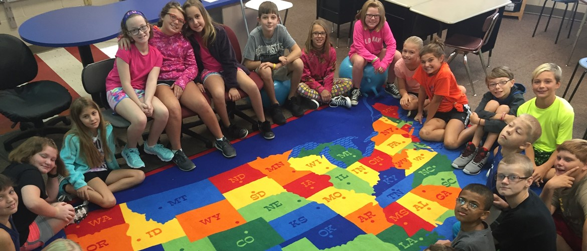 Students sitting on USA map rug.