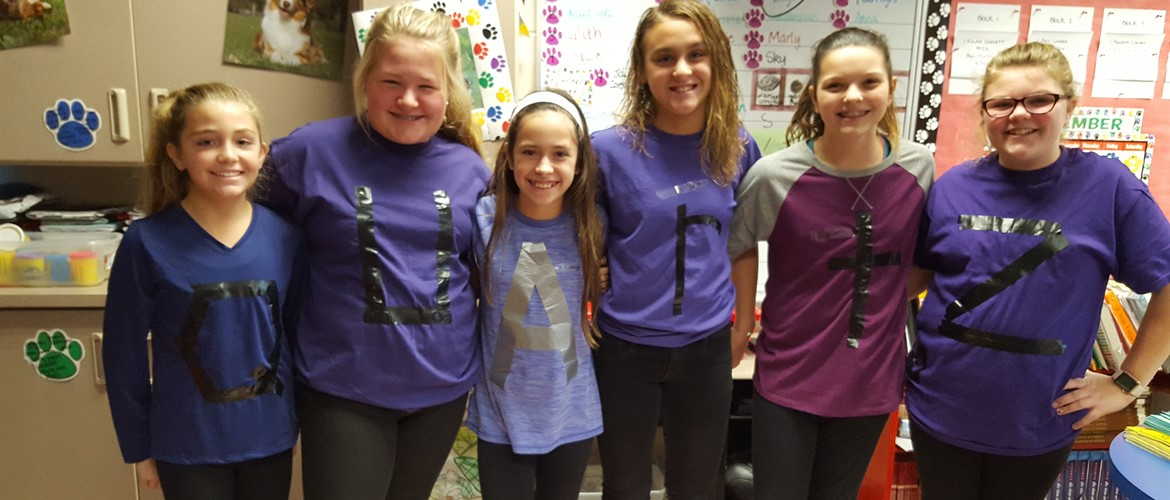 Sixth graders with Scrabble letters on their shirts.