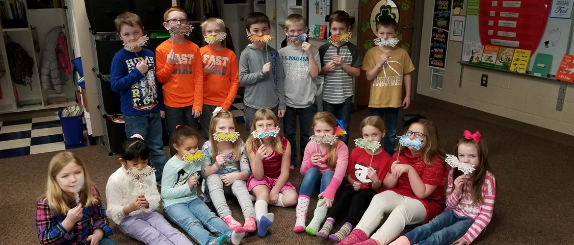 Students with Lorax mustaches ready for Read Across America week.