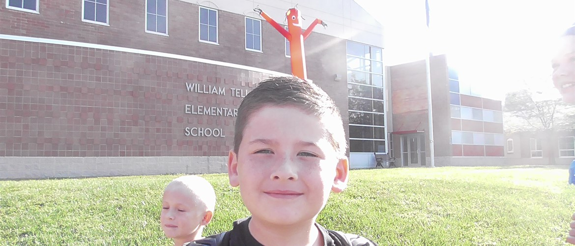 Landon with Big red in front of school.