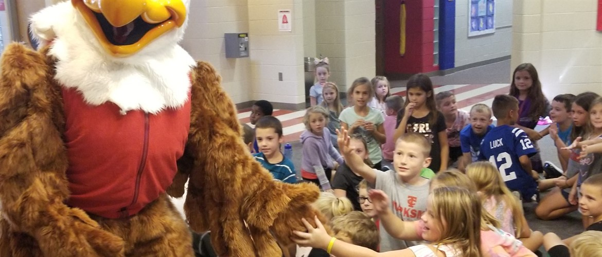 Eddie the Eagle mascot high fives second graders.