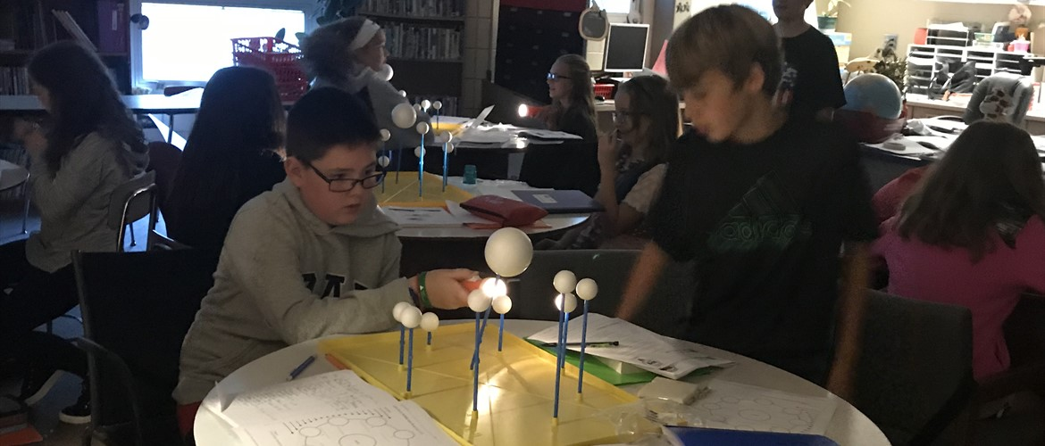 Students using styrofoam balls as celestial objects to study moon phases.