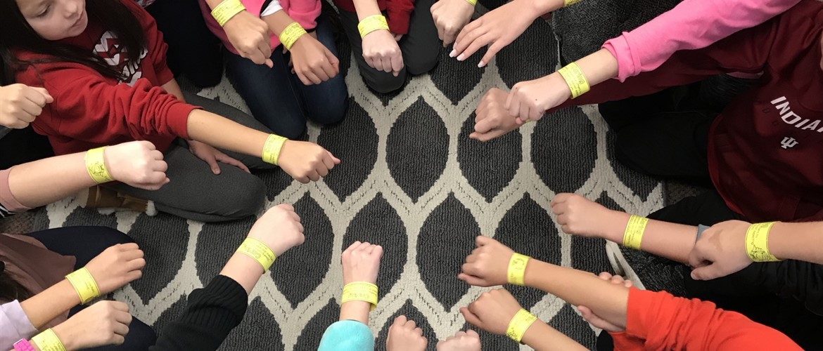 Students showing Caring bracelets they made for November's Life Skill of the month.