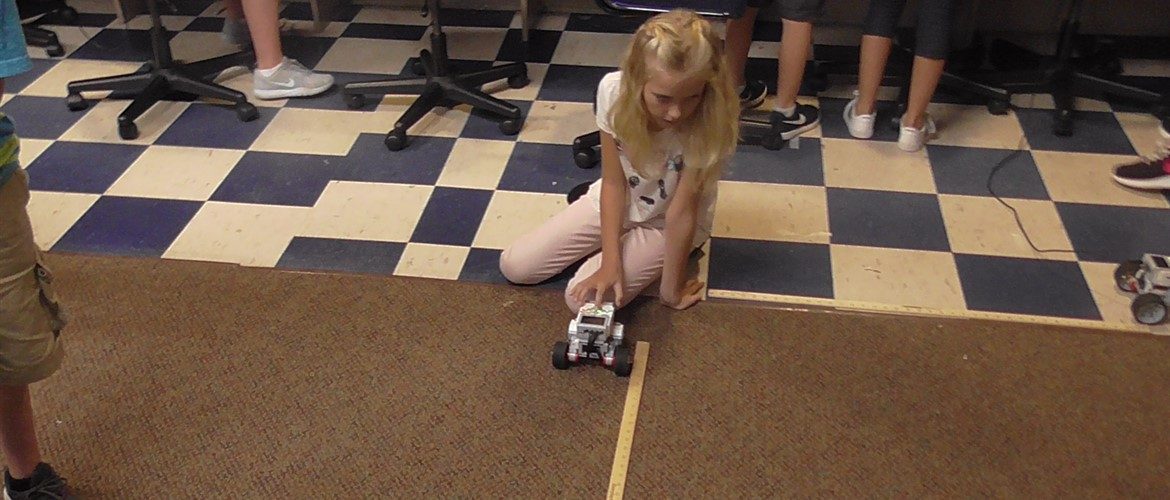 Student working with a robot and a yardstick.
