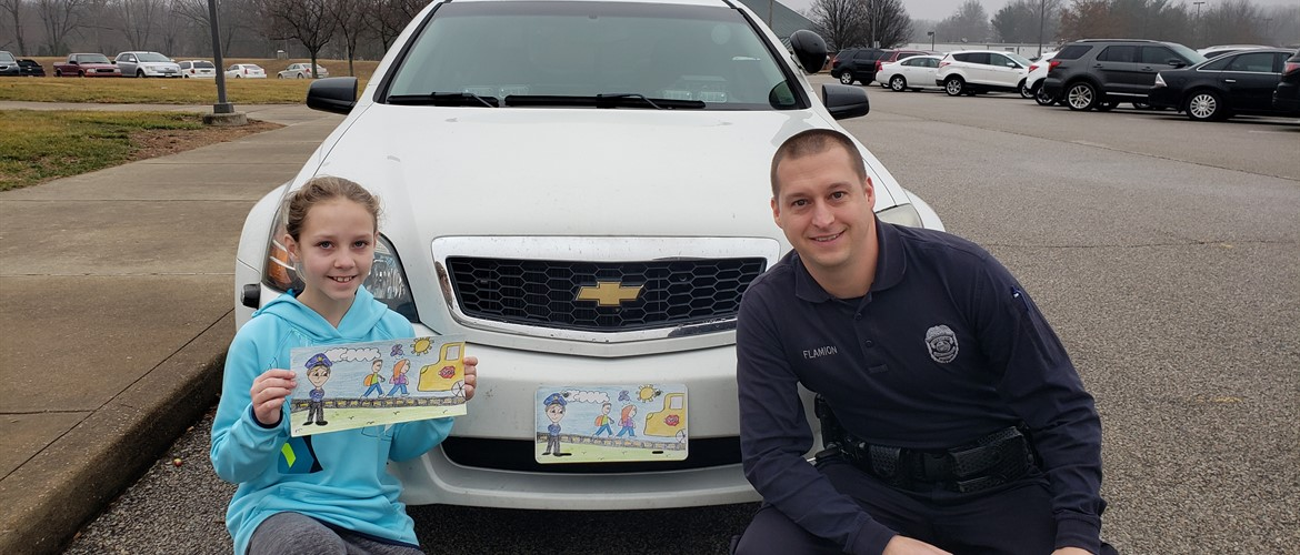 Student with her artwork that is on the license plate of SRO vehicle.